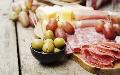 Charcuterie assortment and olives on wooden background